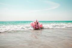 O homem está tendo o divertimento no flutuador inflável da associação do flamingo do rosa fotografia de stock