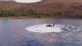 O homem está tendo o divertimento, voando sobre a água em um flyboard, sob a pressão da água Tiro video aéreo, ` s do pássaro video estoque