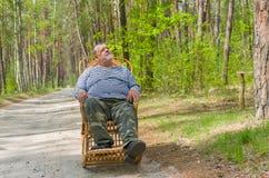O homem está tendo o resto na floresta que senta-se em uma balançar-cadeira de vime foto de stock