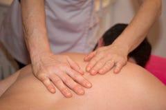 O homem está tendo uma massagem em um centro do bem-estar Imagens de Stock Royalty Free