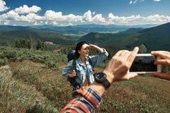 O homem está tomando a foto da mulher que caminha nas montanhas fotos de stock royalty free