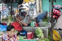 O homem está tomando uma sesta em um mercado de produto fresco da rua em Chau Doc, Vietname imagens de stock