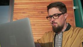 O homem está trabalhando com o portátil na varanda aberta de sua casa, datilografando o texto vídeos de arquivo