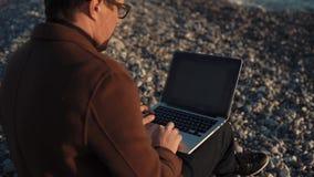 O homem está trabalhando com um portátil senta-se na costa do seixo do mar na noite vídeos de arquivo