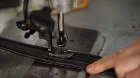 O homem está trabalhando na máquina de costura com couro filme