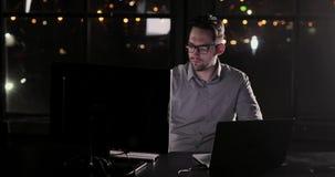 O homem está trabalhando no escritório tarde em horas extras da noite filme
