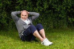 O homem está treinando seus músculos abdominais no prado verde Foto de Stock Royalty Free