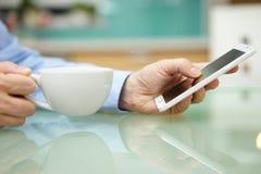 O homem está usando o telefone celular esperto e o café bebendo em casa imagem de stock
