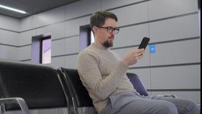 O homem está usando o smartphone que senta-se no aeroporto video estoque