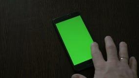 O homem está usando um smartphone com uma tela verde que se encontre na tabela vídeos de arquivo