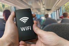 O homem está usando Wifi livre no ônibus com smartphone Imagens de Stock
