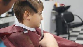 O homem é estando e de fatura o corte de cabelo para o menino pequeno vídeos de arquivo