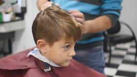 O homem é estando e de fatura o corte de cabelo para o menino pequeno filme