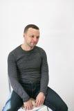 O homem europeu adulto novo está sentando-se em uma cadeira fotos de stock royalty free