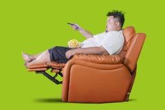 O homem excesso de peso come a pipoca durante a tevê do relógio imagens de stock