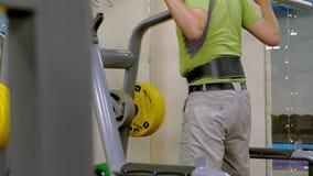O homem excesso de peso faz ocupas com ocupas com um disco do peso para um barbell Homem da aptid?o training Conceito saud?vel do video estoque