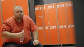 O homem excesso de peso gordo está sentando-se no banco após o treinamento esgotado do exercício no clube de aptidão filme