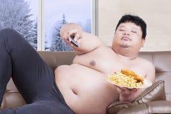 O homem excesso de peso olha a tevê na estação do inverno Fotos de Stock Royalty Free