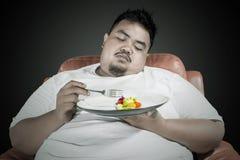 O homem excesso de peso preguiçoso come o alimento saudável imagem de stock royalty free