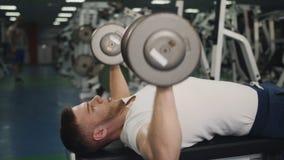 O homem executa pesos de levantamento do exercício para os bíceps que encontram-se no close-up do banco filme