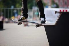 O homem executa um truque do skateboarding Fotos de Stock