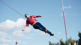 O homem executa uma rotação em torno da corda esticada acima da terra Metragem muito fresca vídeos de arquivo