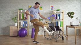 O homem expressivo alegre com um pé enfaixado quebrado joga muletas como uma guitarra video estoque