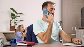O homem fala no telefone celular quando uma mulher olhar a tevê no fundo filme