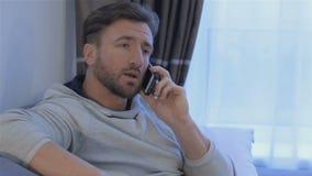 O homem fala no telefone em casa