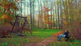 O homem fala pelo telefone no parque no banco vídeos de arquivo