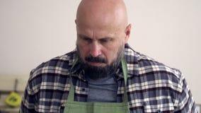 O homem farpado é da aparência caucasiano em sua oficina, vestindo um avental para trabalhar e rola suas luvas vídeos de arquivo