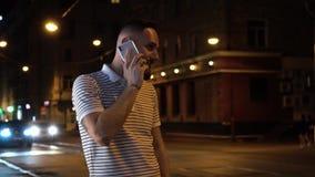 O homem farpado agradável tem uma chamada de telefone celular Responde-lhe e começa-o à conversa com alguém Estada na rua da noit video estoque