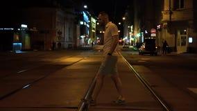 O homem farpado apto considerável em polo listrado e o short verde cruzam a estrada na noite na faixa de travessia video estoque