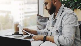 O homem farpado atrativo novo do moderno senta-se no café na frente do aptop, documentos de papel da leitura O Freelancer trabalh fotografia de stock royalty free