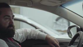 O homem farpado bem sucedido atrativo do retrato que senta-se no veículo e inspeciona comprou recentemente auto do carro filme