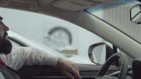 O homem farpado bem sucedido atrativo do retrato que senta-se no veículo e inspeciona comprou recentemente auto do carro video estoque