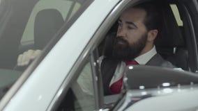 O homem farpado bem sucedido do retrato que senta-se no compartimento de passageiro do veículo novo inspeciona o interior do rece video estoque