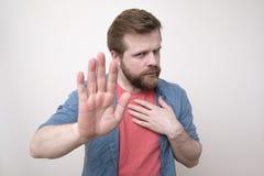 O homem farpado, caucasiano olha fixamente e acalma-se, com um gesto da mão da parada No fundo branco foto de stock