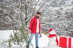 O homem farpado com boneco de neve est? levando a ?rvore de Natal na madeira Um homem novo consider?vel com homem da neve leva um fotos de stock