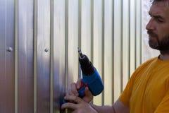 O homem farpado com uma chave de fenda em suas mãos parafusa o perfil do metal Imagens de Stock Royalty Free