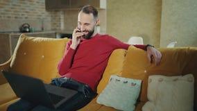 O homem farpado considerável está trabalhando com laptotp em casa Está falando com os clientes no telefone celular e no café bebe video estoque