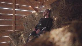O homem farpado considerável nos vidros que respiram expira uma nuvem do vapor que senta-se no feno Fazendeiro novo que descansa  video estoque