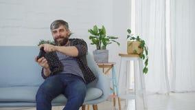 O homem farpado considerável que veste a roupa ocasional está jogando o jogo de vídeo que senta-se no sofá em casa Tecnologias mo video estoque