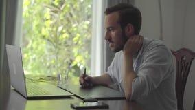 O homem farpado da habilidade considerável tira usando a tabuleta gráfica que olha em um portátil Mão masculina que tira a produç video estoque