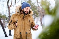 O homem farpado de sorriso veste a roupa morna e a utilização do inverno do smartphone com conexão de dados rápida do Internet no foto de stock