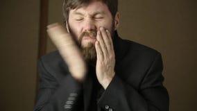 O homem farpado do executivo empresarial veste um revestimento, bocejando e agitando de um frio em um next day após um partido an filme