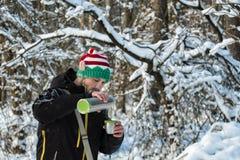 O homem farpado em um chapéu do duende na floresta derrama o chá quente de uma garrafa térmica imagem de stock royalty free
