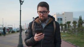 O homem farpado está dando uma volta na cidade e está lendo sms em seu smartphone video estoque