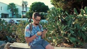 O homem farpado está descansando no parque no dia de verão, está sentando-se no banco e está jogando-se o telefone vídeos de arquivo