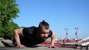 O homem farpado está fazendo empurra levanta durante seu treinamento exterior da manhã Treinamento urbano da aptidão video estoque
